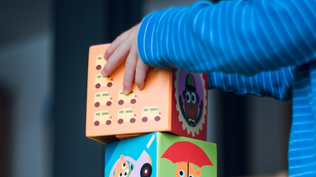imagen de un niño jugando con un rompecabezas (solo se ven los brazos y parte del juego). Decorativa, para ilustrar el post juegos para tratar la falta de atención en niños